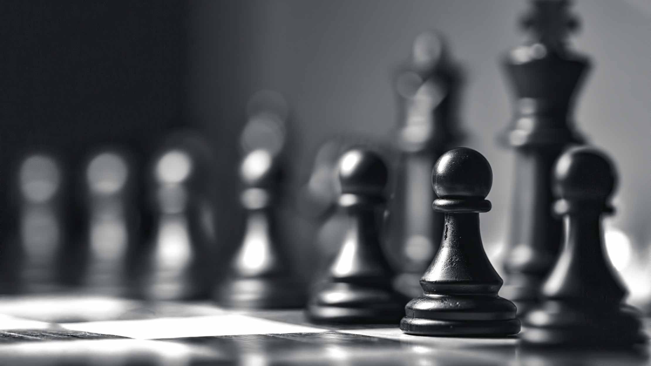 Black and white image of chess pieces on chessboard